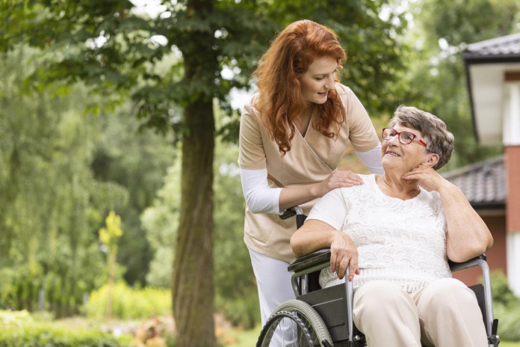 Une aide soignante qui pousse une personne en fauteuil roulant