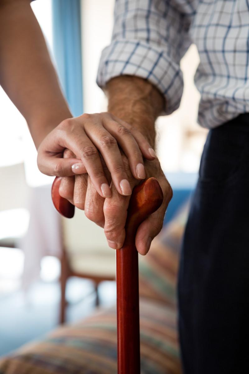 personne agéee tenant une canne avec une perssonne jeune qui pose sa main sur lui