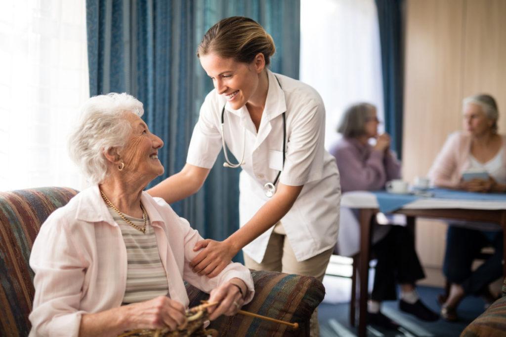 Aide Soignante sourie à une personne agée